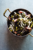 Southern stewed collard greens with red onion and chunks of fresh pork