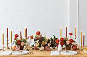 Festlich gedeckter Tisch mit roter Blumendeko, Früchten und Kerzen