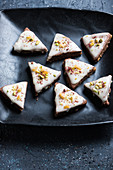 Vegan chocolate slices filled with orange cream, decorated with icing, pistachios, candied oranges and raspberry powder