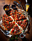 Tomato pizza with olives, sliced on a wooden table
