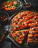 A tomato pizza with olives and pine nuts