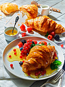 Croissants served with honey and summer berries
