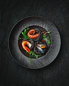 Sepia spaghetti with seafood on a black plate