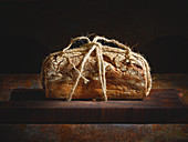 A rustic loaf of bread tied with string on a wooden board