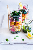 Pasta salad with kale and roasted vegetables in a jar, drizzled with kale pesto and a squeeze of lemon