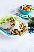 Vegan kale burrito on a plate with veggies pico de gallo sauce, salad and kale pesto