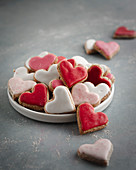 Pink, red and white heart-shaped biscuits on a plate