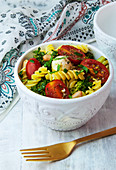 A bowl of vegetarian pesto pasta salad with mozzarella, broccoli and tomatoes