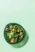 Oriental spinach salad with croutons, raisins and mint