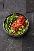 A salad bowl with salmon and green asparagus