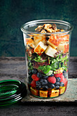 A layered salad with berries and halloumi