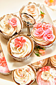 Festive cupcakes decorated with cream topping and sugar flowers
