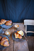 Croissants with cappuccinos on a rustic wooden table
