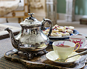 Silver teapot, teacups and pastries on tray