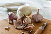 Onions, garlic and folding knife on wooden board