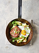 A steak pan with bok choy and a fried egg