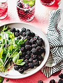 Blackberries and mint leaves on the white plate