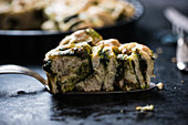 A slice of vegan yeast cake stuffed with spinach and walnuts