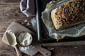 Loaf of delicious rye bread with seeds lying on timber tabletop