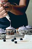 Frau garniert Blaubeercupcakes mit Frosting aus dem Spritzbeutel