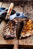 Sticky Spareribs mit hausgemachter BBQ-Glasur auf Holzbrett