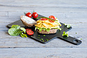 A bread roll with scrambled eggs, salad and tomatoes