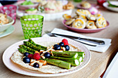 Roasted green asparagus with berries and croutons on a tortilla