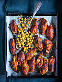 Spicy chicken wings with chickpeas on an oven tray
