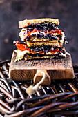 A sandwich with grilled vegetables (peppers, red cabbage, tomatoes) and cheese