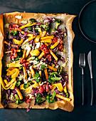 Potato and broccoli salad with bacon and mango on an oven tray