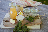 Ingredients and glass jars for thyme jelly with apple juice on a wooden table