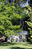 Gartenhäuschen etwas versteckt unter hohen Bäumen
