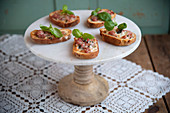 Crostini with salsiccia and taleggio on a cake stand