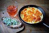 Omelette with carrots frying-pan sandwich, glass towel