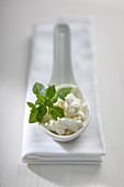 Crumbled feta with fresh oregano on a porcelain spoon