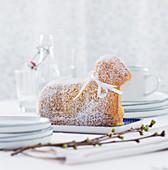 Gebackenes Osterlamm mit Puderzucker und Schleifchen auf Tisch