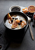 Chia seeds pudding with slices of orange, mandarins and olives in bowl