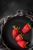 Red and fresh strawberries flat lay in black dish