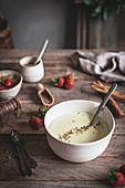 Porridge mit Gewürzen und Erdbeeren auf Holztisch
