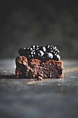 Ein Stück Schokoladenkuchen ohne Mehl mit Brombeeren und Heidelbeeren