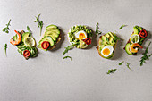 Variety of sandwiches with sliced avocado, sun dried tomatoes, egg, shrimps and arugula