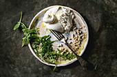 Sliced Italian burrata cheese, fresh arugula salad, pine nuts and olive oil in white ceramic plate