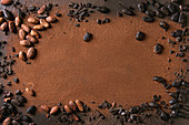 Variety of fresh and dry cocoa beans with chopped dark chocolate over cocoa powder as background