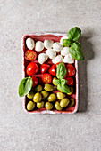 Mozzarella, cherry tomatoes, green olives antipasto appetizers served with basil