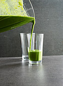 Green smoothies being poured into glasses