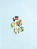 Stilleben mit Gewürzen, Kräutern, Nüssen, Ölen und Trockenfrüchten