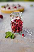 Fresh wild strawberries in a glass jar