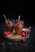 Two glasses of vegan chocolate mousse decorated with fresh raspberries