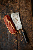 A cleaver and bacon on a wooden background