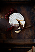 Camembert with redcurrants on a wooden table